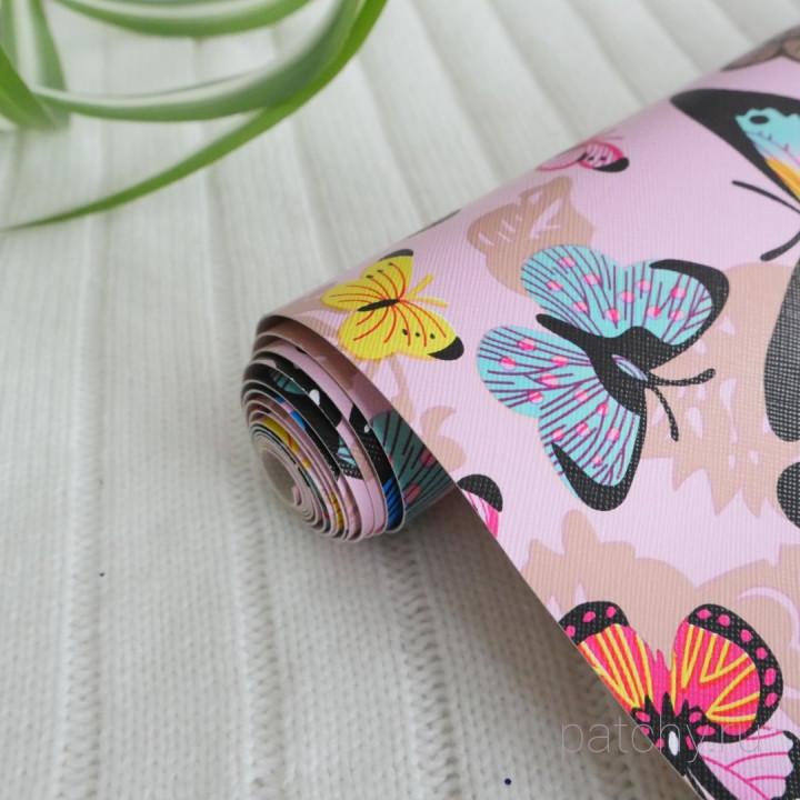 Кожзам разноцветные бабочки на бледно розовом